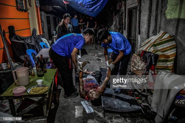 Funeral workers carry away the body of a suspected drug pusher who was killed by unknown assailants in Navotas Metro Manila Philippines April 1 2018...