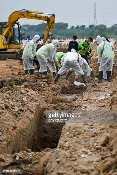 Funeral workers lower the coffin of a victim of the Covid-19 coronavirus at Rorotan cemetery in Jakarta on July 22, 2021.