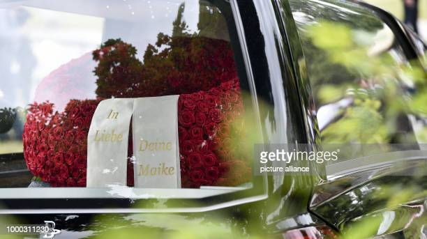A funeral wreath with the lettering 'In Liebe Deine Maike' can be seen inside a car in the convoy accompanying the remains of former German...
