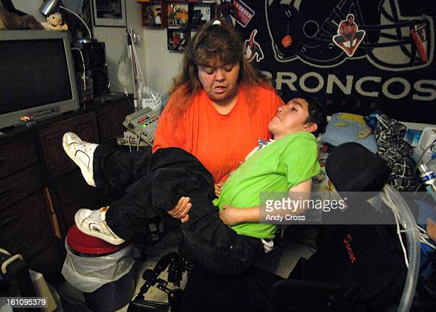 FUNERALa Eric Roybal's aunt Iris VanVelkinburg <cq> lifts Eric from his bed to his wheelchair at their house Thursday afternoon Eric 18yearsold and...