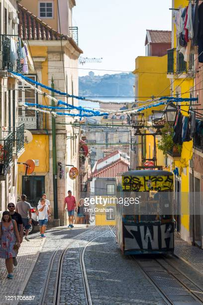 Funicular Elevador da Bica with graffiti carrying local people and tourists climbs steep hill in City of Lisbon Portugal