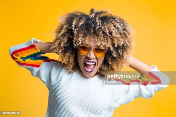 funky afro junge frau vor gelbem hintergrund - 70er jahre frisur stock-fotos und bilder