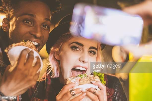 Funky friends eating burgers in pub