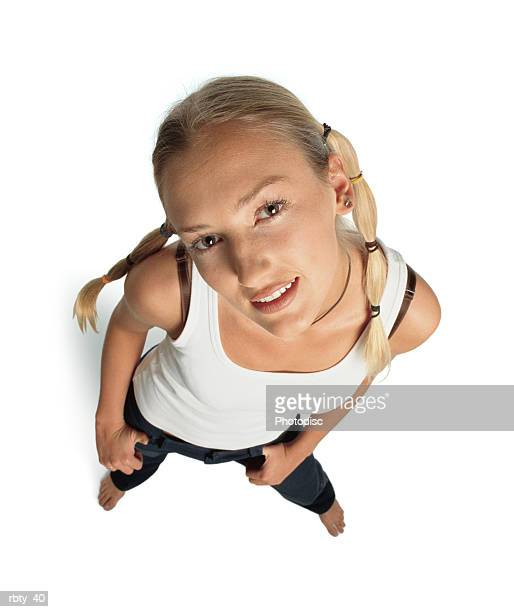 funky teenager with funny blonde hair in pigtails and brown eyes wearing a white tank top and dark pants looks up into the camera with a slight smile as she tilts her head to the side and puts her hands in her pockets - 若い女性一人 ストックフォトと画像