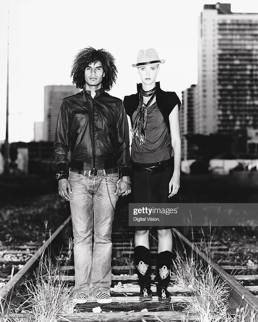 Funky Twentysomething Couple Standing Side by Side on an Urban Railway Track : Stock Photo