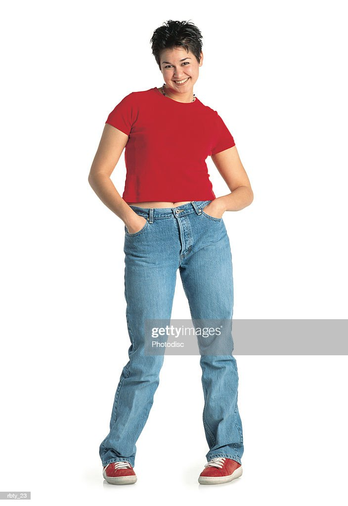 funky young female with dark hair and white skin wearing a red small shirt and blue jeans with red sneakers smiles at the camera and pulls a funny pose : Foto de stock