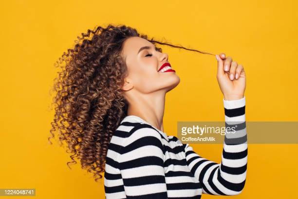 funky jong meisje tegen gele achtergrond - gekruld haar stockfoto's en -beelden