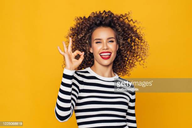 funky young girl against yellow background - ok sign stock pictures, royalty-free photos & images