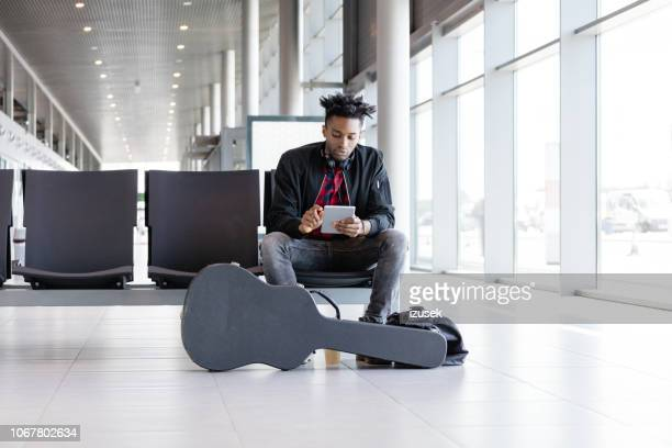 funky young man waiting for flight in airport lounge - maxim musician stock photos and pictures