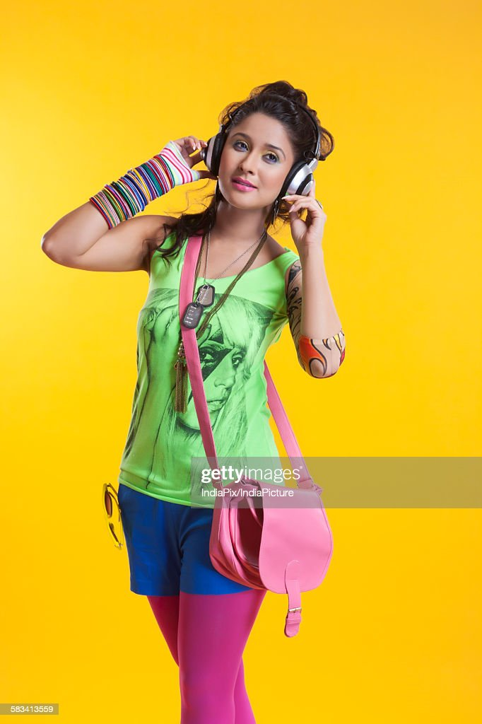 Funky young woman listening to music : Stock Photo