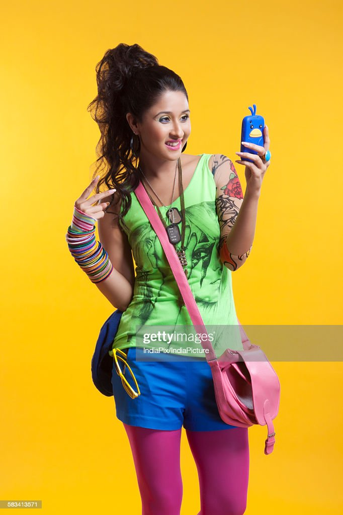 Funky young woman reading sms on mobile phone : Stock Photo