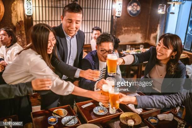 楽しい日本人の友達が居酒屋で良いニュースを乾杯 - 仕事後 ストックフォトと画像