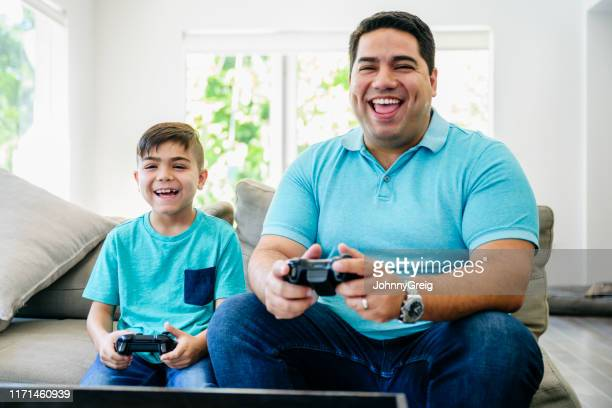 fun-loving latin american father and son playing video games - close to stock pictures, royalty-free photos & images