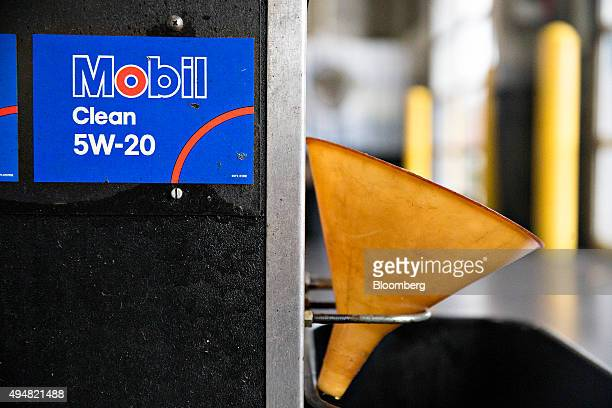 A funnel hangs next to a bank of Exxon Mobil Corp brand motor oil dispensers in an automotive repair shop in Rockford Illinois US on Wednesday Oct 28...