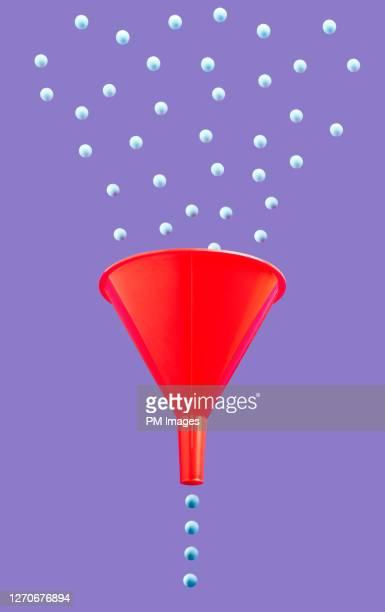 funneling little blue balls - pursuit concept stock pictures, royalty-free photos & images