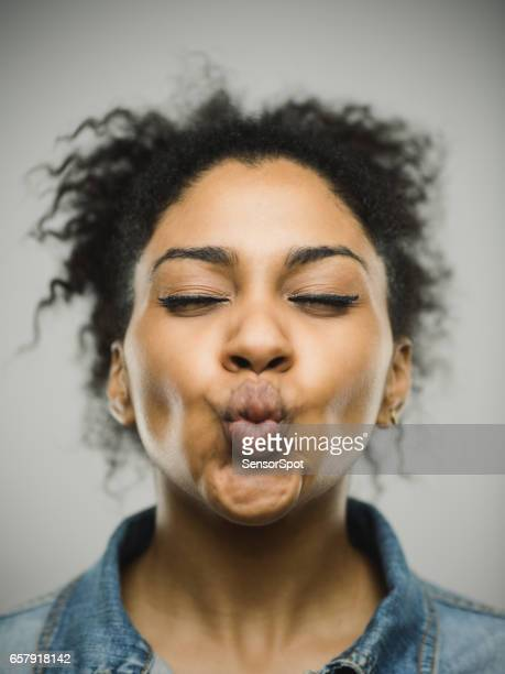 funny afro american woman against gray background - puckering stock photos and pictures