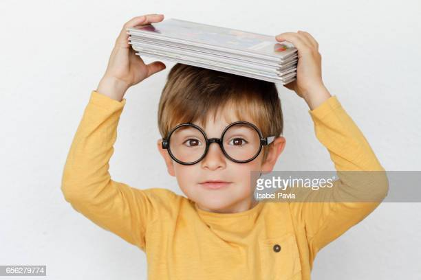 Funny boy holding stacked books on head