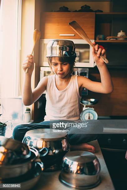 Funny boy playing drums in the kitchen