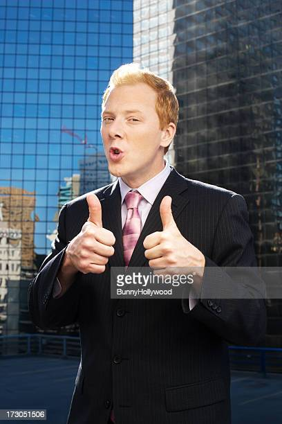 funny businessman gives it two thumbs up on roof