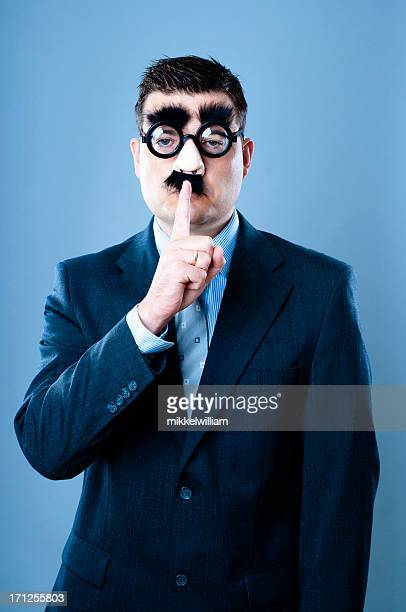funny businessman makes a sign to be quiet - groucho marx stock photos and pictures
