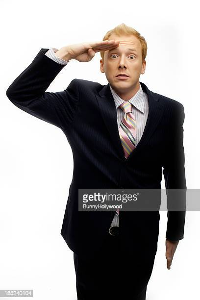 Funny businessman saluting on White