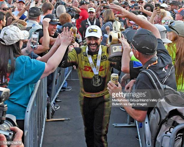 Funny Car winner JR Todd celebrates with fans in Pomona on Sunday November 11 2018 at the 54th annual NHRA Finals at Auto Club Raceway Todd also won...