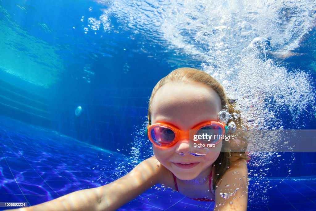 Funny child in goggles dive in swimming pool : Stock Photo