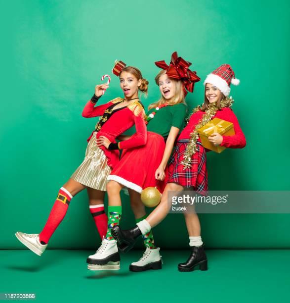 grappige kerst portret van drie tiener meisjes tegen groene achtergrond - izusek stockfoto's en -beelden
