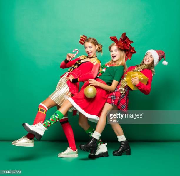 grappig kerstmisportret van drie tienermeisjes tegen groene achtergrond - izusek stockfoto's en -beelden