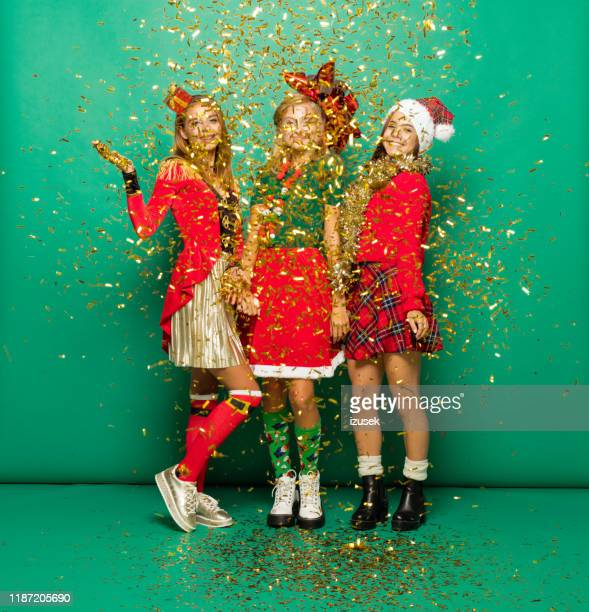 funny christmas portrait of three teenage girls among confetti against green background - izusek stock pictures, royalty-free photos & images