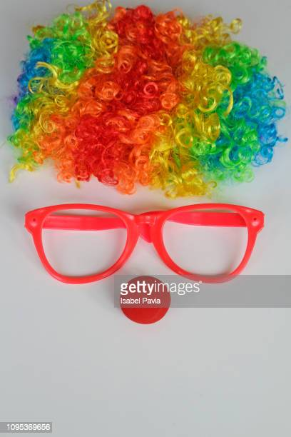 funny clown face formed with colorful wig, glasses and red nose on white background - clown stock-fotos und bilder