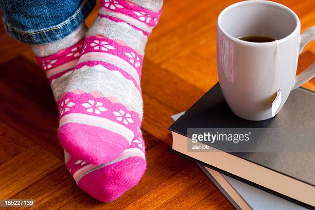 Funny colored socks with cup of tea and books.