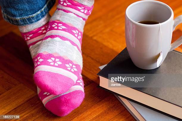 Lustige bunte Socken mit Tasse Tee und Bücher.