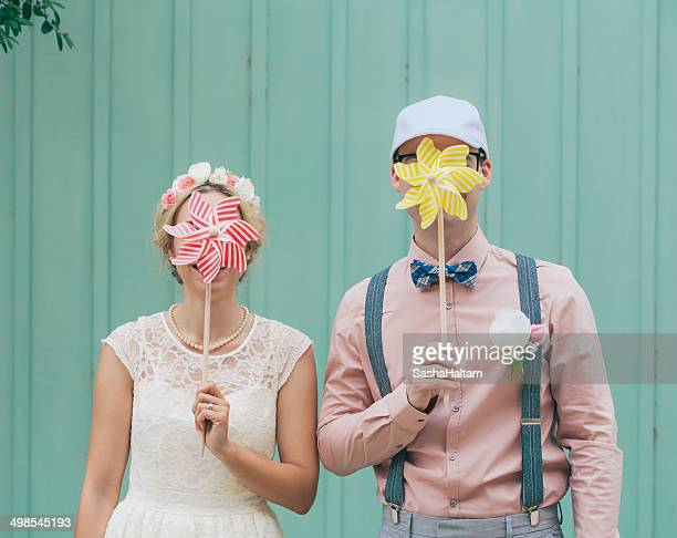 Funny couple cover faces with pinwheel