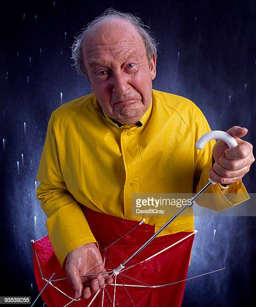 funny crying man with broken umbrella is soaked and miserable.