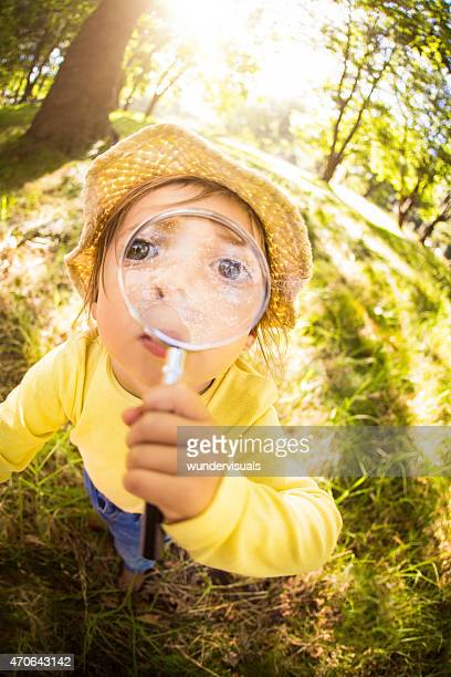 Funny curious toddler holding magnifying glass up to her face