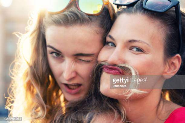 Funny faces of of best girlfriends on vacation with hair mustaches