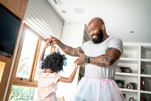 Funny father with tutu skirts dancing like ballerinas 1181326104