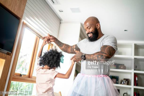 funny father with tutu skirts dancing like ballerinas - fathers day stock pictures, royalty-free photos & images