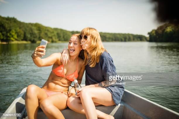 funny female friends taking selfie on boat ride - bateau de plaisance photos et images de collection