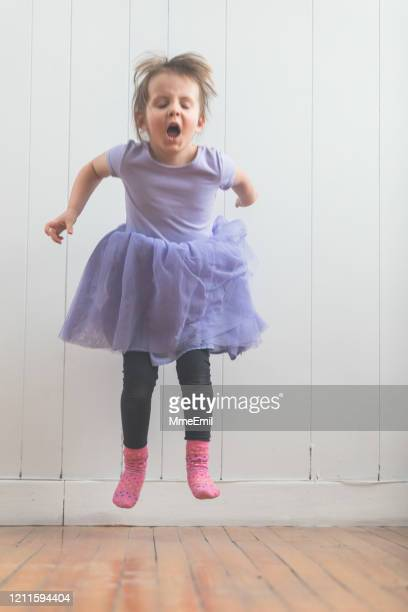 funny four years old girl jumping and dancing - mmeemil stock pictures, royalty-free photos & images