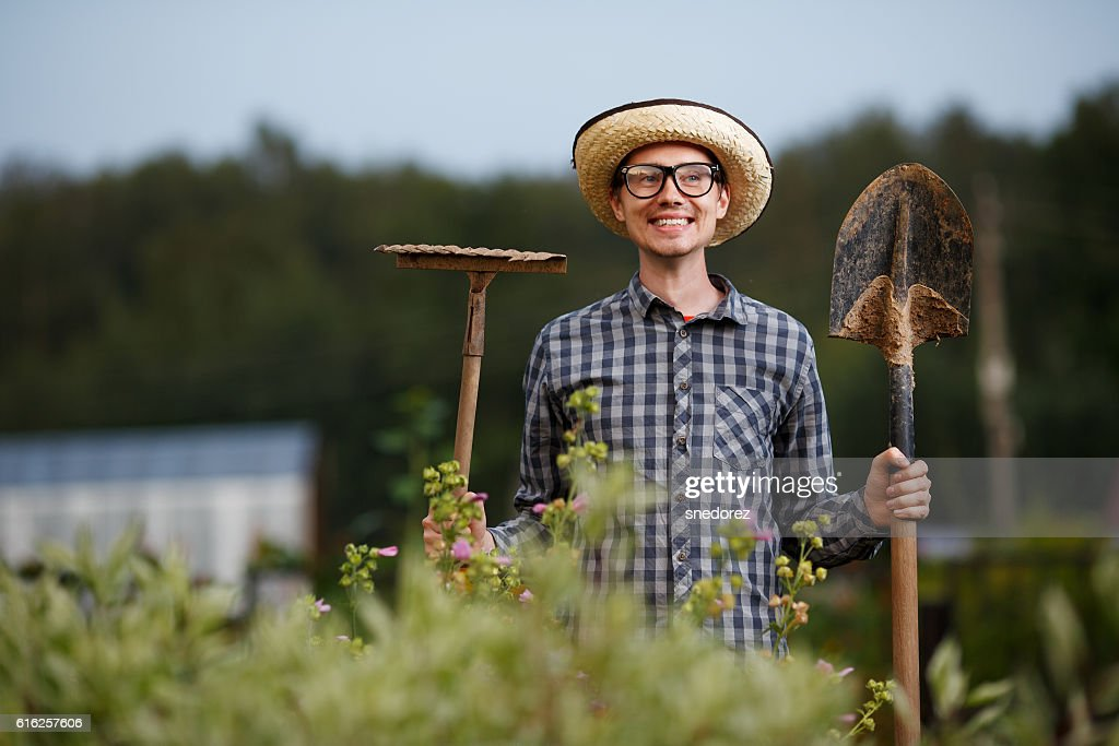 Funny gardener holding a shovel and rake outdoors : Foto de stock