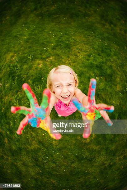 Funny girl with colorful finger paint on hands