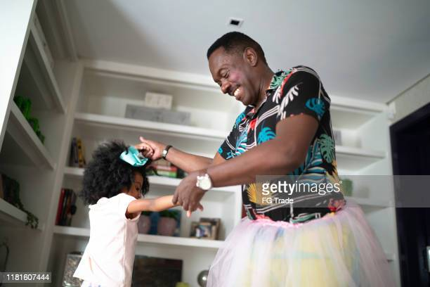 funny grandfather with tutu skirts dancing like ballerinas with grand daughter - mask dance stock pictures, royalty-free photos & images