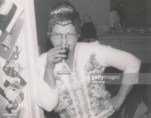 funny grandmother wearing wig and drinking alcohol at holiday party 1950s vintage photograph - 1950 1959 stock pictures, royalty-free photos & images