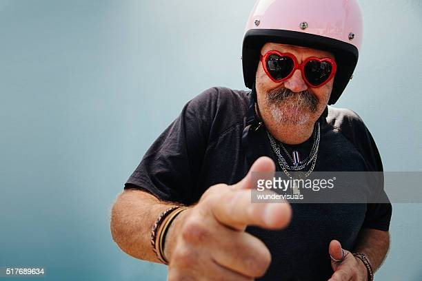 funny grandpa with pink helmet and heart sunglasses - practical joke stock photos and pictures