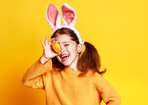 funny happy child girl with easter eggs and bunny ears on yellow 1133811820