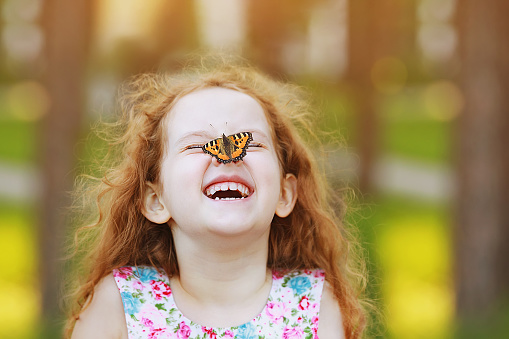 Funny laughing curly girl with a butterfly on his nose. 842921614