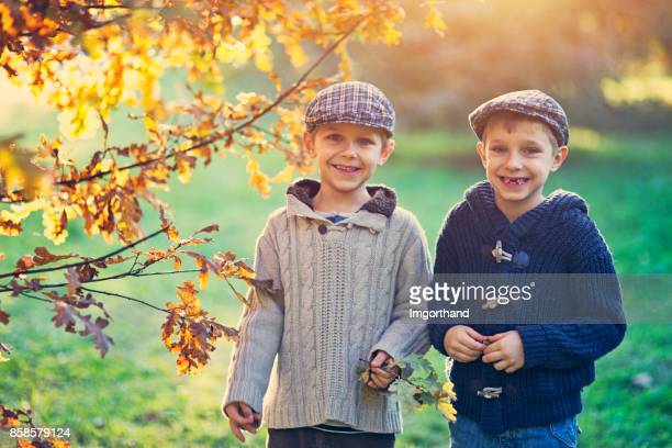 Funny little brothers in autumn park