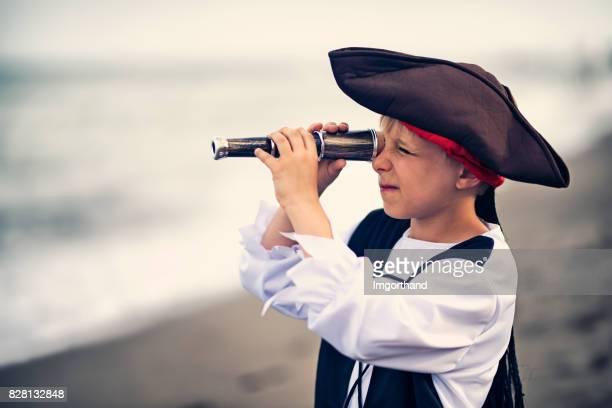 Grappige kleine piraat op de verkeerde manier met spyglass is zoek